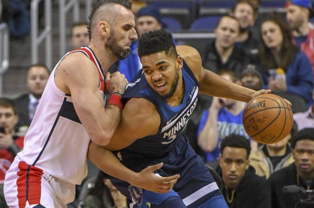 Minnesota Timberwolves center Karl-Anthony Towns (32) works to the basket against Washington Wizards center Marcin Gortat (13) in the first half on March 13 at Capital One Arena in Washington, D.C. Photo by Mark Goldman/UPI