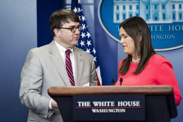Acting Veterans' Affairs secretary Robert Wilkie accepts President Trump's donation of his 2018 first quarter salary from White House Press Secretary Sarah Sanders during a press briefing at the White House on Thursday. Photo by Pete Marovich/UPI