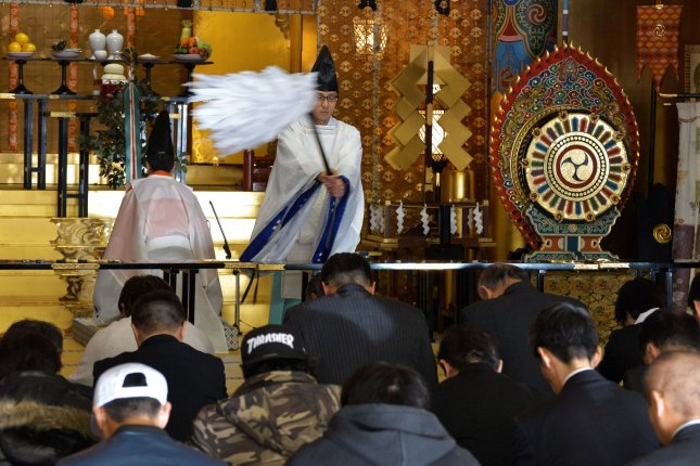 A Shinto priest performs the Oharai ritual for office workers during a ceremony at Kanda Myojin shrine in Tokyo on January 4, 2017. On December 15, 1945, U.S. Gen. Douglas MacArthur ordered an end to state Shintoism in Japan, a key belief of which was that the emperor was a divine being. File Photo by Keizo Mori/UPI