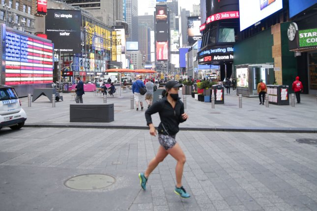 A runner jogs through Times Square in New York City on Thursday. Photo by John Angelillo/UPI