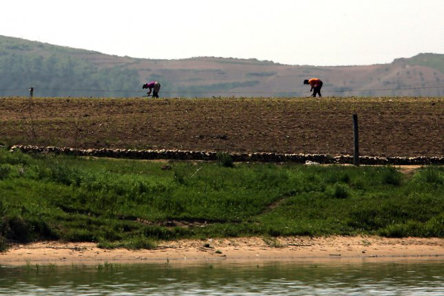 North Koreans work in the fields near the North Korean city Sinuiju, across the Yalu River from Dandong, China's largest border city with North Korea. Soil degradation due to intensive cultivation has been one of many problems in the country's agriculture. File Photo by Stephen Shaver/UPI