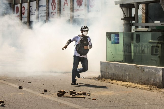 A protester runs as police fire tear gas during a protest against the military coup in Mandalay, Myanmar. At least 18 people were killed and 30 injured in protests Sunday. Photo by Xiao Long/UPI