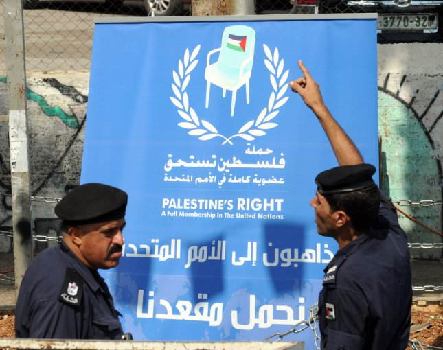 Palestinian police stand in front of a banner announcing the unveiling of a large symbolic United Nations seat in central Ramallah, West Bank, September 20, 2011. Palestinian President Mahmoud Abbas will address the United Nations on Friday, September 23, 2011, in a bid for Palestine to attain the status of a full member state in the UN. UPI/Debbie Hill