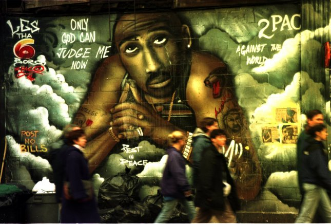 NYP97021704-17FEB97-NEW YORK,NEW YORK,USA: The release of Rap artist Tupac Shakur last film Gridlock'd garnered him rave reviews and renewed interest in what might have been for the rapper slain in 1996.However everyone doesn't share that same thought as this group of tourist stroll through the lower east side in Manhattan,February 16th, and ignore the rappers memorial mural. UPI ep/Ezio Petersen