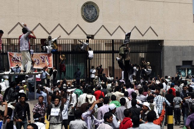 Protesters climb a fence at the United States embassy in Sanaa in Yemen on September 13, 2012. (UPI/Mohammad Abdullah)