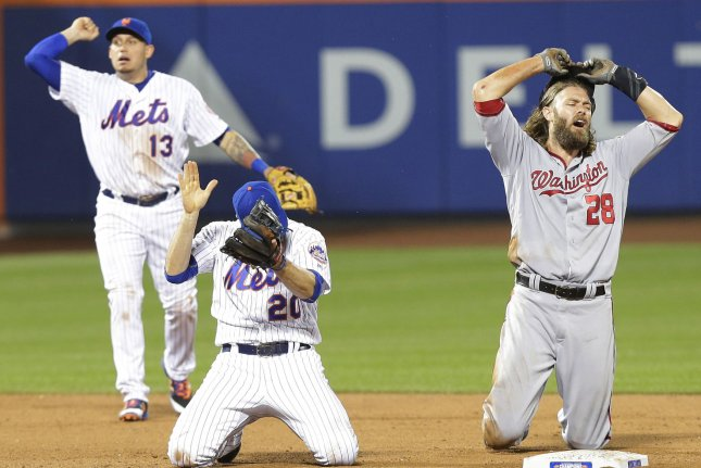 New York Mets' Neil Walker and Asdrubal Cabrera celebrate while Washington Nationals' Jayson Werth reacts and throws his helmet after a double play in the 9th inning at Citi Field in New York City on July 7, 2016. The Mets defeated the Nationals 9-7. Photo by John Angelillo/UPI