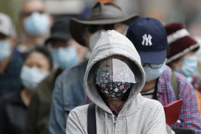 TD Bank customers wear protective face masks as they wait in line to enter a Chinatown bank branch in New York City in May. Photo by John Angelillo/UPI