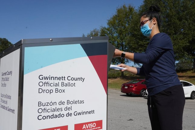 Emily Sado drops her absentee ballot in a dropbox on Election Day at Shorty Howell Park in Lawrenceville, Georgia, November 3, 2020. File photo by Tami Chappell/UPI