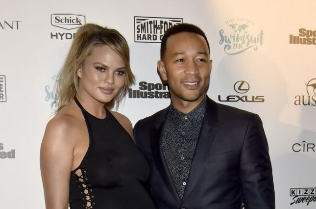 Chrissy Teigen (L) and husband John Legend at the 2016 Sports Illustrated swimsuit issue fan festival on February 17. The couple are expecting a daughter in the spring. File Photo by Gary I. Rothstein/UPI