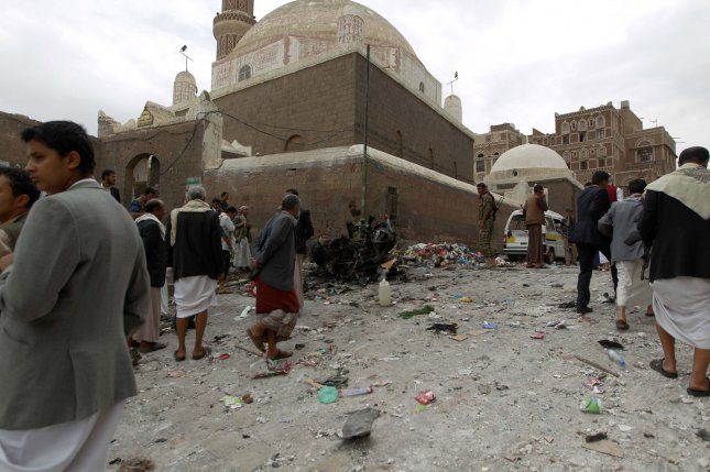 Yemenis surround the wreckage of a vehicle outside the Kobbat al-Mehdi Shiite mosque in Sanaa on June 20, 2015. A cease-fire this week is expected to bring a significant pause in fighting in Yemen's five-year civil war. File Photo by Mohammad Abdullah/UPI