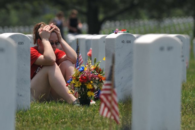 A woman visit a gravestone in section 60 at Arlington National Cemetery in Arlington, Virginia on Memorial Day, May 31, 2010. UPI/Kevin Dietsch