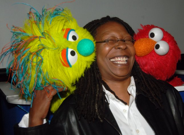 Actress Whoopi Goldberg poses with the new muppet Azibo (L) and Elmo (R) after a news conference to announce Panwapa, a new world wide initiative from Sesame Street Workshop to cultivate the next generation of globally responsible children, at the United Nations International School in New York on October 10, 2007. (UPI Photo/Ezio Petersen)