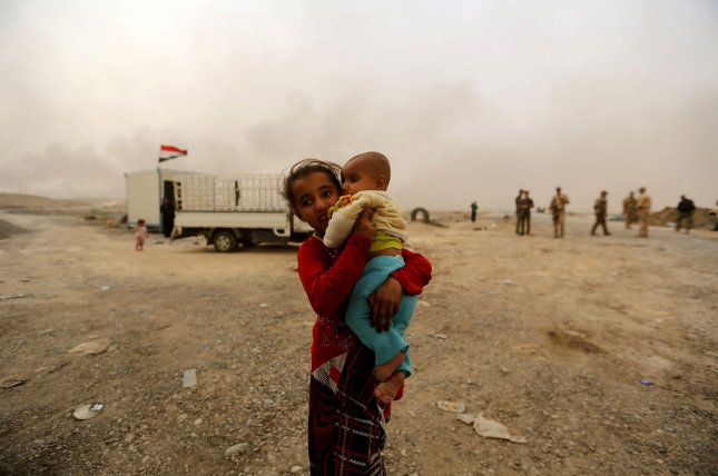 Children born in Mosul in the past two years do not have the legal documents verifying they are Iraqi citizens because they were born under rule by the Islamic State, which is accused of committing war crimes and crimes against humanity, authorities said. In this image, Iraqi civilians flee from fighting while the smoke rise in the background from burning oil fields damaged during fighting between Iraqi security forces and the Islamic State in Qayara, near Mosul, on November 1. Photo by Murat Bay/UPI