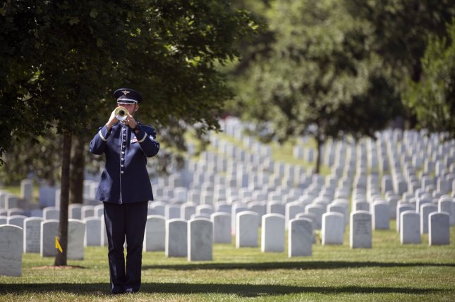 An Air Force Honor Guard bugler plays Taps at Arlington National Cemetery in Arlington, Va., on June 8. Three U.S. military trainers died Friday in a shooting incident when their vehicle failed to stop at the gate at King Faisal Air Base in Jordan. File Photo by Kevin Dietsch/UPI