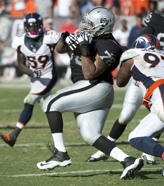 Oakland Raiders tackle Donald Penn runs with a Derek Carr pass that was deflected by the Denver Broncos. Photo by Terry Schmitt/UPI