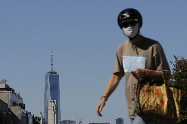 A pedestrian wears a face mask and helmet when crossing the street with a view of One World Trade Center in New York City on Monday. Photo by John Angelillo/UPI