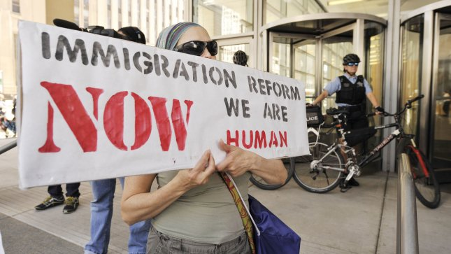 A protester holds a sign as Chicago Police stand guard outside of the new Immigration and Customs Enforcement court building on May 15, 2012 in Chicago. The protest was held as part of weeklong demonstrations leading up to the NATO summit being held on May 20 and May 21 in Chicago. UPI/Brian Kersey