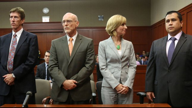 George Zimmerman listens as the verdict is announced that the jury finds him not guilty, with Mark O'Mara (left), co-counsel, Don West and Lorna Truett, on day twenty-five of his trial in the Seminole circuit court in Sanford, Florida, July 13, 2013. The jury deliberated for sixteen hours aver two days. UPI/Joe Burbank/Pool