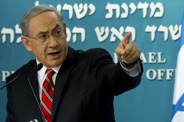 Israeli Prime Minister Benjamin Netanyahu looks at a video screen showing Hamas militants firing rockets into Israel from crowded, residential areas in the Gaza Strip, during a press conference in his Jerusalem offices to foreign correspondents on August 6, 2014. UPI/Jim Hollander