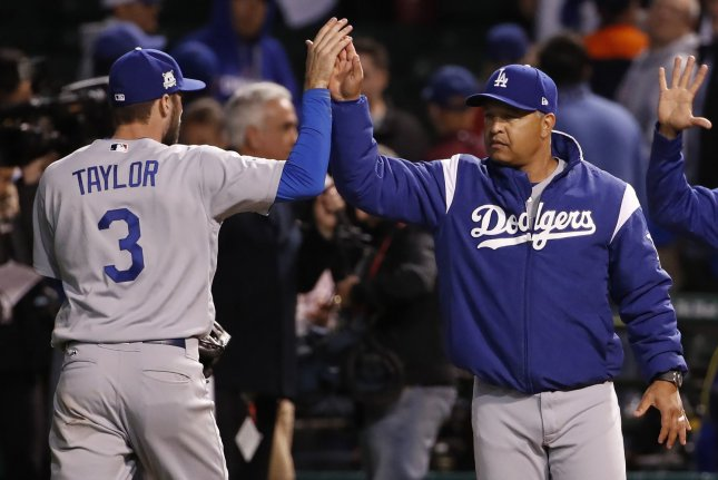 Los Angeles Dodgers manager Dave Roberts high fives Chris Taylor (3) after defeating the Chicago Cubs in game 3 of the National League Championship Series at Wrigley Field in Chicago on October 17, 2017. The Dodgers beat the Cubs 6-1 to take a 3-0 series lead. Photo by Kamil Krzaczynski/UPI