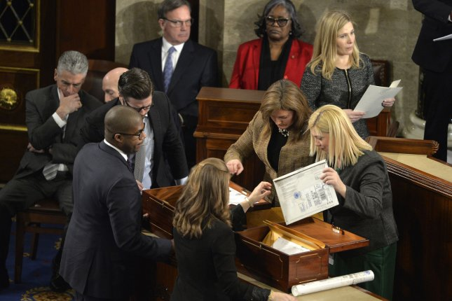 Congressional staff unseal envelopes from the two ballot boxes that contain 50 states and District of Columbia Electoral College votes on the floor of the House to be counted and validated at the U.S. Capitol on January 6, 2017. The procedure, established by the Constitution, and presided over by Vice President Joe Biden and Speaker Paul Ryan declared and finalized Donald Trump and Mike Pence as president and vice president. File Photo by Mike Theiler/UPI