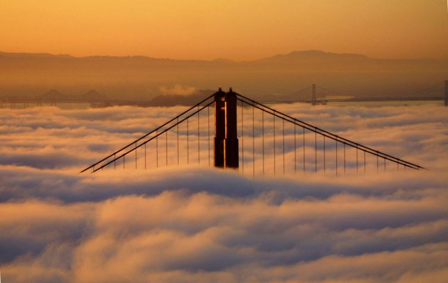 The North tower of the Golden Gate Bridge sticks out of the fog at sunrise on April 25, 2001. The world famous bridge opened on May 27, 1937. File Photo by Terry Schmitt/UPI