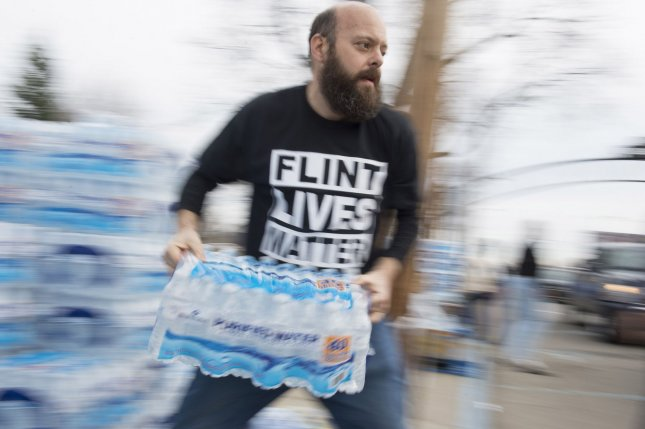 Volunteers distribute cases of water at City Hall in Flint, Mich., on March 12, 2016, as lead in the city's water piples made tap water undrinkable. A Gallup poll shows that 63 percent of Americans, the majority of them minorities and people who earn less than $30,000 a year, worry a great deal about pollution in drinking water. File Photo by Molly Riley/UPI