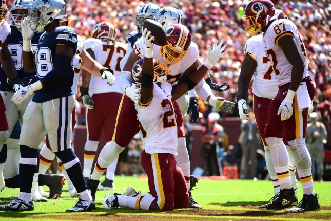 Washington Redskins running back Adrian Peterson (26) celebrates with teammates after rushing for a 1-yard touchdown against the Dallas Cowboys in the first quarter Sunday at FedEx Field in Landover, Maryland. Photo by Kevin Dietsch/UPI