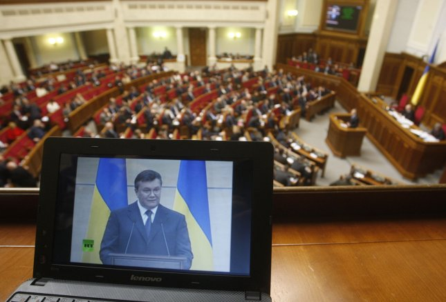 Ousted Ukrainian President Yanukovich is seen on laptop screen during his news conference in Rostov-on-Don of Russia as Ukrainian Prime Minister Arseniy Yatsenyuk speaks in the parliament in Kiev on March 11, 2014 a day ahead of his visit to United States. UPI/Ivan Vakolenko