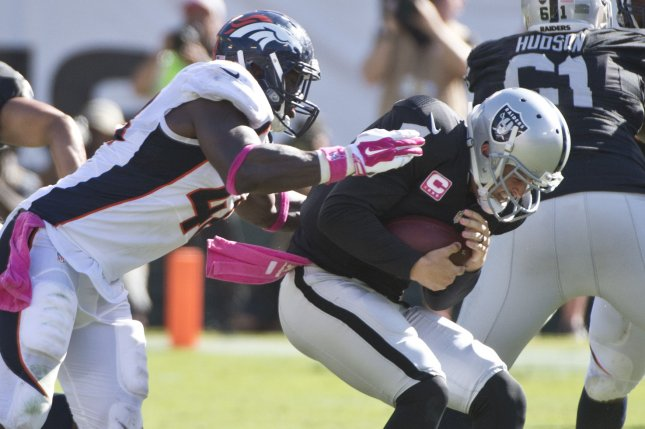 Oakland Raiders QB Derek Carr (R) is sacked by Denver Broncos' Shaquil Barrett for a loss of seven yards in the third quarter at O.co Coliseum in Oakland, California on October 11, 2015. The Broncos defeated the Raiders 16-10. Photo by Terry Schmitt/UPI