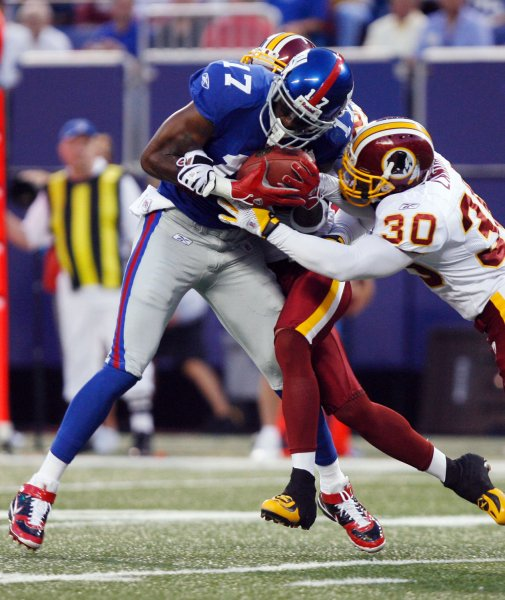 New York Giants Plaxico Burress makes a reception and is tackled by Washington Redskins Laron Landry (30) in the first quarter at Giants Stadium in East Rutherford, New Jersey on September 4, 2008. The Giants defeated the Redskins 16-7. (UPI Photo/John Angelillo) .