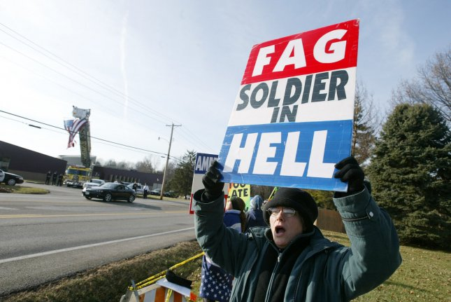 A protester with the Westboro Baptist Church of Topeka, KS, chants as the funeral procession for U.S. Army Pvt. Peter Navarro pulls up to the St. Clare of Assisi Catholic Church in Ellisville, Mo on December 23, 2005. The group led by the Pastor Fred Phelps. protests at the funerals of U.S. servicemen and women claiming that God is punishing those that fight in the Iraq war. Navarro was killed by a roadside bomb on December 13 in Iraq. (UPI Photo/Bill Greenblatt)