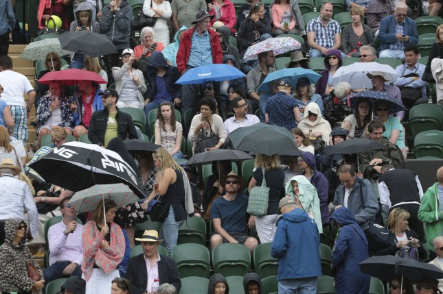 Spectators shield themselves from the rain at Wimbledon. New research suggests chronic pain symptoms are influenced by the weather -- particularly rain and a lack of sunshine. Photo by Hugo Philpott/UPI