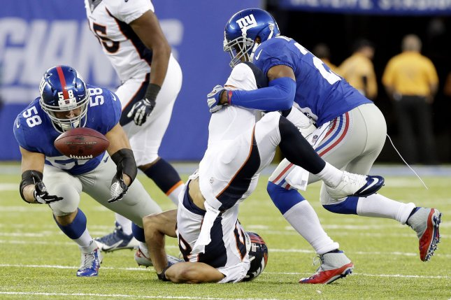 New York Giants linebacker Mark Herzlich (58) fails to intercept a pass intended for former Denver Broncos wide receiver Eric Decker, who gets upended in the second half in Week 2 of the NFL season on September 15, 2013 at MetLife Stadium in East Rutherford, New Jersey. File photo by John Angelillo/UPI
