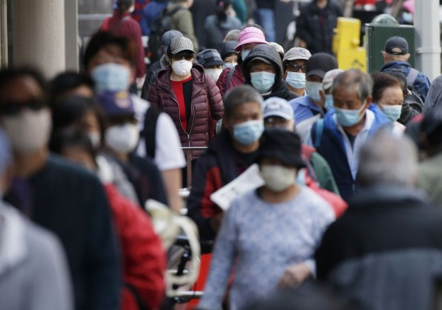 People gather and form a line for food distribution in the Chinatown section of Manhattan during the COVID-19 pandemic in New York City in May. Photo by John Angelillo/UPI
