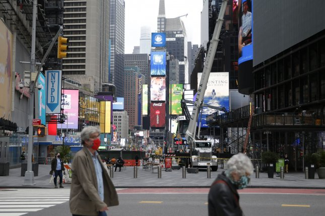 Masked pedestrians walk through Times Square in New York City. Gallup's survey Tuesday said Americans over the past two months apparently became more open to receiving an approved coronavirus vaccine. File Photo by John Angelillo/UPI