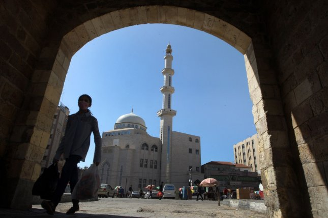 A Palestinian girl walking in front of Al-Kabir mosque on The first day of Ramadan, in Khan Yunis in the southern Gaza Strip on Tuesday. Photo by Ismael Mohamad/UPI