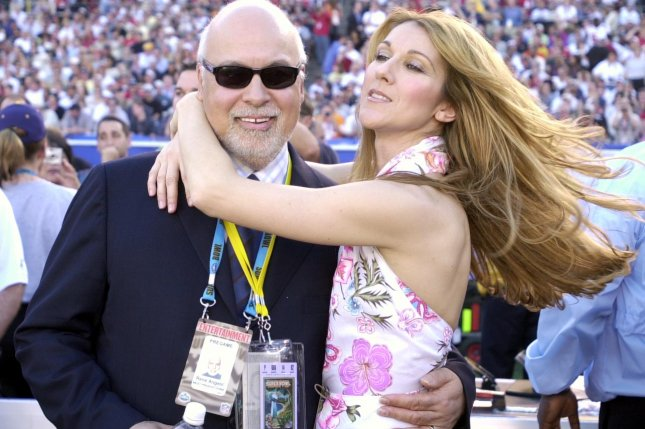 Singer Celine Dion hugs husband Rene Angelil before performing during pre-game ceremonies at Super Bowl XXXVII, on Jan. 26, 2003 in San Diego. Photo by Earl Cryer/UPI