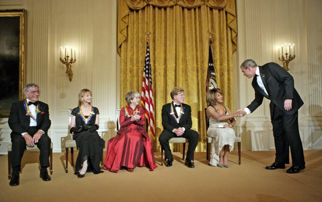 President George W. Bush congratulates Tina Turner during a reception for the Kennedy Center Honors in the East Room of the White House on December 4, 2005. From left, the honorees are singer Tony Bennett, dancer Suzanne Farrell, actress Julie Harris, actor Robert Redford and singer Tina Turner. (UPI Photo/Eric Draper/White House)