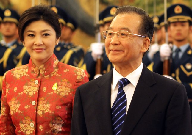 Chinese Prime Minister Wen Jiabao (R) escorts Thai Prime Minister Yingluck Shinawatra past a military honor guard during a welcoming ceremony in the Great Hall of the People in Beijing, April 17, 2012. UPI/Stephen Shaver