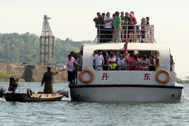 A North Korean man sells contraband pickled eggs, cigarettes, alcohol and ginseng to Korean, Japanese and Chinese tourists on the Yalu River, north of Dandong, China's larger border city with North Korea. The North Korean regime is expected to launch economic reforms involving five-year plans in May 2016. File Photo by Stephen Shaver/UPI