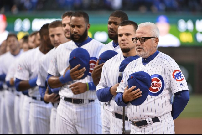 Chicago Cubs manager Joe Maddon (R) stands with his team during the singing of the National Anthem. Photo by Brian Kersey/UPI