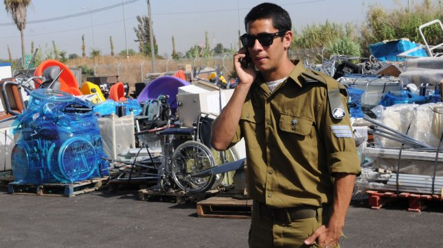 An Israeli soldier walks in front of humanitarian aid at the Zrifin Military Base in Rishon le-Zion. UPI File Photo/Debbie Hill