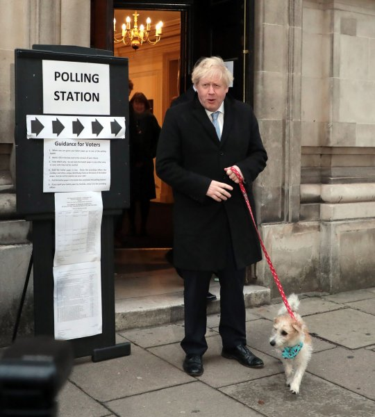 British Prime Minister Boris Johnson and his dog leave a polling station in Westminster Thursday after casting a ballot in Britain's third general election in four years. Photo by Hugo Philpott/UPI