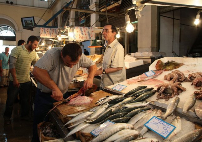 A salesman guts fish in the busy fish market in Athens on June 16, 2012. UPI/Hugo Philpott