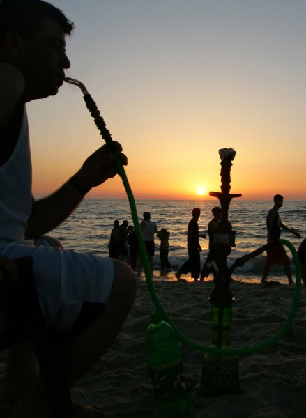 A Palestinian man smokes a hookah as Palestinians enjoy the beach as the sun sets during the second day of a truce in Gaza City on June 20, 2008. Guns went quiet as a six-month truce between Israel and Gaza militants took effect early Thursday. (UPI Photo/Ismael Mohamad)