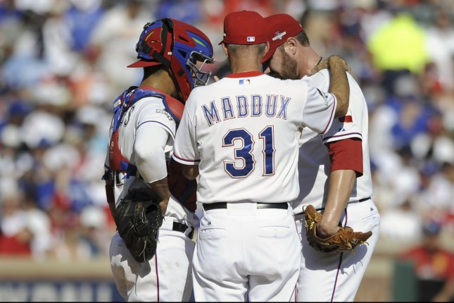 Texas Rangers catcher Robinson Chirinos (L) and pitching coach Mike Maddux visit pitcher Colby Lewis in the fourh inning of game 4 of the ALDS at Rangers Ballpark in Arlington, Texas on October 12, 2015. Photo by Michael Prengler/UPI