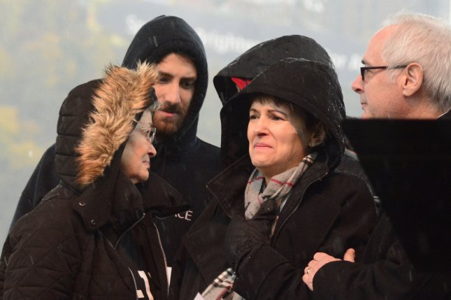 Family members of the Tree of Life synagogue shooting victims look out at the crowd at the Rally for Peace in Point State Park in Pittsburgh on Friday, the same day Jeffrey Clark, a supporter of the shooting suspect, was arrested in Washington, D.C.