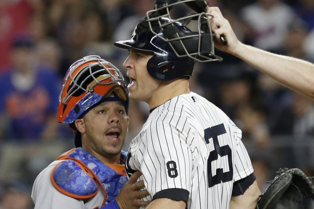 New York Yankees' Mark Teixeira reacts and is held back by New York Mets catcher Rene Rivera after he is hit by a pitch from Steven Matz at Yankee Stadium in New York City on August 3, 2016. Photo by John Angelillo/UPI
