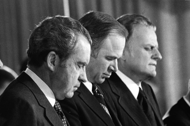 President Richard Nixon (L) bows his head during the closing prayer at the annual National Prayer Breakfast at the Washington Hilton on Feb. 1, 1973. With him are Rep. Albert H. Quie, R-Minn. (C), and Billy Graham, who delivered the prayer. UPI File Photo